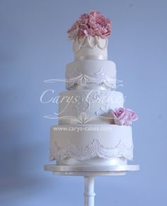 4 tier vintage styled wedding cake with dusky pink flowers and edible pearls. Two of the tiers have edible lace decoration. This was delivered to Manor Park, Clydach