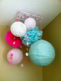 DIY Tutorial: Paper Lantern and Tissue Pom Mobile   Baby Lifestyles. [Done! I made a triangle out of wood dowels and then hung 7 lanterns off. It looks awesome!]