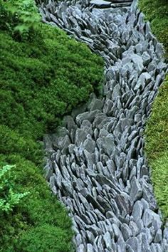 Once you've cleared the creek area you wish to fill with rocks and lined it with fabric, turn the flat stones on their sides and begin to fill the space in a line form.