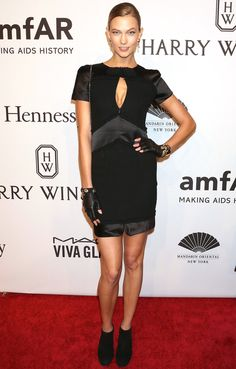 Karlie Kloss in a black keyhole Chanel little black dress, fingerless gloves and booties