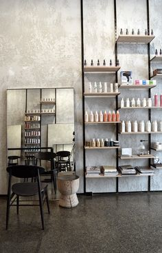 The polished concrete, the textured wall, the stool, the industrial shelving