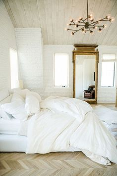 White brick bedroom with gold mirror and chandelier