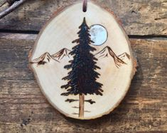 Full moon mountain scene with pine tree ornament or small wall hanging. Wood burned and painted wood slice.