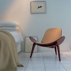 "Designed by Hans J. Wegner in 1963, the CH07 is sculptural easy chair with a triangular footprint. The chair is frequently placed where it can be viewed from all sides, on its own or in groups.Sometimes called ""The Smiling Chair"", the three-legged construction provides absolute stability; the chair achieves a floating lightness due to its wing-like seat and the arching curves of its tapered legs."