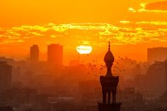 Sunset in Cairo from Al-Azhar Garden, Egypt. The Pyramids behind two buildings in background - stock photo
