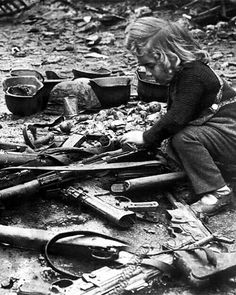 Little girl playing with guns left on streets of Berlin after war in 1945. Note the MP44s in the foreground, the precursor to AK-47.