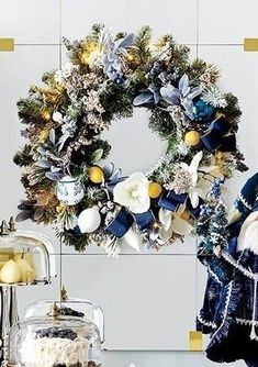 "Inspired by the blue and white palette of delftware, the Delft Blue Indoor Cordless 31"" Wreath offers an unexpectedly fresh departure for holiday decorating. The milky tones of exquisitely lifelike lamb's ear, blueberries, pine and cypress form a soft backdrop for vibrant magnolia blooms and lemons. The arrangement is then dotted with jeweled picks, glass ornaments and ribbon, illuminated by 140 warm white LED lights."