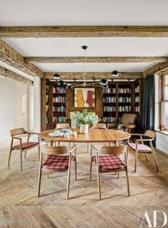 A painting by Jennifer Christy overlooks the dining area; the light fixture is by David Weeks Studio, the Hans J. Wegner table is from Suite New York, and the Maruni chairs are from Cite | archdigest.com