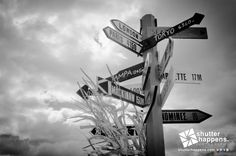 Which Way To Go? by Mark David Zahn Photography (formerly Shutter Happens Photography).  The directional sign at Egg Harbor's marina points in all directions against a stark, cloudy fall afternoon. Corn stalks adorn the sign during the Pumpkin Patch Festival, one of Door County's busiest festivals.