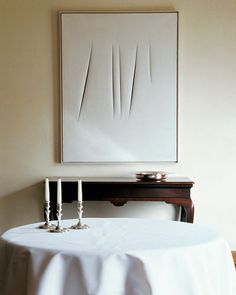 ~Axel Vervoordt - A work by Lucio Fontana with an antique table in a home in Belgium. Photo: Christian Savramon. ELLE DECOR