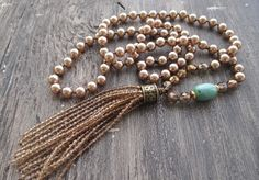 Hand-knotted glass pearls in a pretty light bronze neutral. Turquoise bead accent with an ombre glass tassel. Dress it up or down. Its the perfect