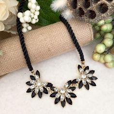 ✂️$18JUST IN Black Clear Flower Necklace Necklace: Faux gold tones plated Lobster clasp Clear and black acrylic stones Twisted fabric chain NWOT and comes with dust bag. Jewelry Necklaces