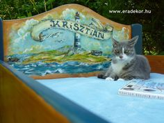 Berci cica rendkívül jól érzi magát a hajóskapitány kényelmes ágyán - Krisztián névreszóló tömörfenyő, hajós mintával festett gyerekágy. Fotó azonosító: AGYKRI12