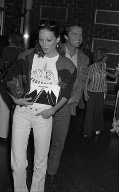 Embracing a youthful look, Huston wears light jeans, a T-shirt, and cropped jacket at the 1974 premiere of *The Parallax View.* Her drop earrings and round-rimmed glasses add a dose of glamour to the outfit. Jack Nicholson, Anjelica Huston, Evolution Of Fashion, Stylish Couple, Light Jeans, Musa, Perfect Woman, Celebs, Celebrities