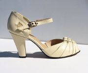 Glamorous 1920's replica high heel sandal with gathered and knotted leather vamp details. - Leather uppers with leather soles - Whole and half sizes 5 ½-11 (Runs long; everyone goes down at least a ha