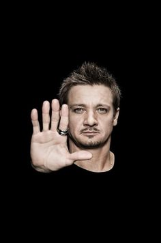 Jeremy Wearing Black T-Shirt Against a Black Background Holding Right Hand Up in Front of Him