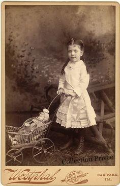 jouets d'enfants, jeux de photographes : Petite fille avec sa poupée dans une poussette. Ph...