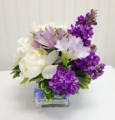 Wedding table centerpiece. White peonies, lavender stock, freesia, and alstromeria. Designed by Rebekah