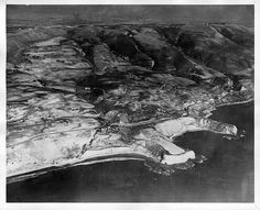"Aerial view looking east, with Portuguese Point (center)  and Inspiration Point (right.) According to Ralph Jester's notes on  reverse of photo, ""Vanderlip Cottage is left center, San Pedro Hill, top right. Levinson-Warner house is white house in center. Char's Hill (for Charlotte Vanderlip) is knoll and bluff just across road from Portuguese Point."""