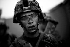 """Bravo Company's Pvt. Cody Lee Ensley walks through the safety of the gates at an American base after a daylong fierce attack by insurgents near Payendi. From the story """"Signs Of Traction In U.S. Fight Against Afghan Taliban"""", 2010."""