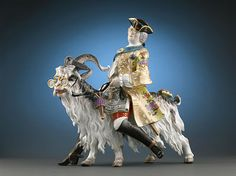 """Meissen """"Count Brühl's Tailor on a Goat"""" 1925. Based on the original one in 1730 by Johann-Joachim Kaendler (Kändler) at Meissen.   The Count's tailor requested and invitation to dine at Court with the King.  The Count did not dare ask the King, so he went to Kaendler and commissioned him to create a statue of the tailor, fulfilling his tailor's wish to dine with the King."""