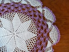 WHITE and VIOLET CROCHETED DOILY. This table mat measures 15 inches in diameter. This cotton lace, crochet mat / doily is intricately detailed. Table doilies can used under floral arrangements, candles, and figurines. Not only decorative, but a crochet doily will protect your furniture. COLORS: White and Light Violet. SIZE: 15 inches in diameter. CARE: Hand wash in warm water, roll in towel and squeeze to drain excess water (do not twist or wring). Shape and lay flat on a clean dry ...