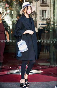 Selena Gomez wears a black dress, black coat, tights, a fedora, and mules