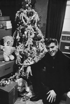 A young Elvis Presley poses in front of a flocked Christmas tree