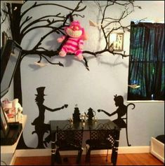 Tea table, mural, tree branch with Cheshire cat plushie. Genius!