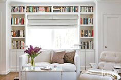Campbell designed built-in shelves to mark a niche in the master bedroom. A table from Lillian August fronts a custom sofa, covered with li...