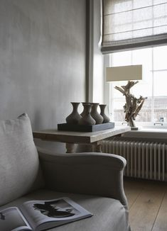 Alexander van Berge - biscuit earthenware vases in a wooden tray, rough wood side table, driftwood table lamp, linen upholstered seating