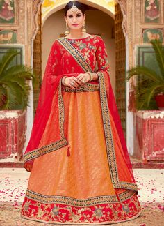 We unfurl our the intricacy and exclusivity of our creations highlighted in this sort of a desirable orange and red jacquard silk lehenga choli. You are able to see some interesting patterns done with embroidered, lace, resham and zari work. Comes with matching choli and dupatta. (Slight variation in color, fabric & work is possible. Model images are only representative.) Banarasi Lehenga, Bridal Lehenga Choli, Lehenga Saree, Bridal Lehenga Online, Lehenga Choli Online, Party Wear Lehenga, Embroidered Silk, Wedding Wear, Bollywood