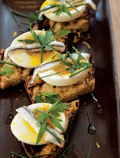 Egg & Anchovy Crostini:    There is no better way to eat an egg with a runny yolk than on a nice piece of grilled bread. Topping the egg with briny anchovy fillets and fresh herbs makes a great bite, and the bread turns the whole package into an extraordinary handheld snack.