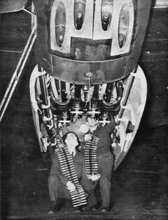 Two ground crew arming the 20mm cannon on a de Havilland Mosquito. This view inside the gun bays shows the hidden complexities of the guns.