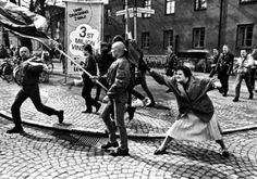 by Hans Runesson A womanhitting a skinhead with her handbag; she had been in a concentration camp during World War II. Växjö, Sweden, April 1985.