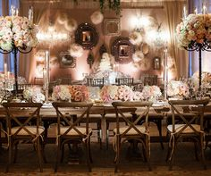 Wooden tables and chairs topped with tall topiaries, tapers and low floral arrangements create a comfortable chic feel.