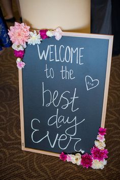 "Black + pink chalkboard wedding sign idea - large black chalkboard with bright pink flower decor with ""welcome to the best day ever"" written on it {Eric Vest Photography, Inc.}"