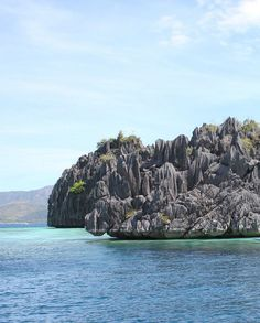 A limestone cliff juts over teal-blue waters outside the Twin Lagoons in Coron.