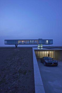 striking-minimal-glass-house-elevated-above-barren-landscape-4-far-night.jpg