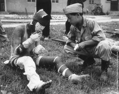 A severely wounded Korean soldier smoking a cigarette in the grounds of an advance casualty cleaning unit, 1950