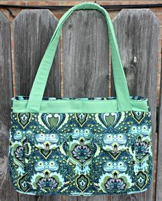 This bag is the perfect complement to the busy woman-on-the go! The design features a pretty gathered flap and front straps. There is also an inner zippered pocket and a padded pocket with a flap, which would be perfect for toting your iPad or other electronic device! Also, complete the removable stiff false bottom for added stability!  The pdf pattern includes 18 pages of sewing instructions, complete with 41 step-by-step color photos.  Click here to read more details about this sewing…