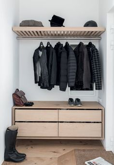 Simple entryway with wood furniture and beautiful shoe and coat storage.