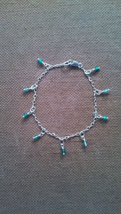 Delicate looking bracelet featuring light and dark aqua agate beads suspended on sterling silver headpins from a sterling silver chain, all finished