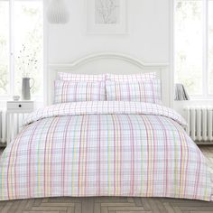 The Iona duvet set offers a contemporary check pattern in bright and beautiful tones. The duvet cover features a mix of pastel lilac stripes, contrasted with pretty teal, pink and yellow lines. The set is fully reversible, offering a white and lilac pink check pattern.