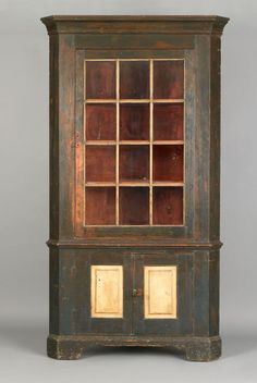 """Realized Price: $3172   Pennsylvania painted 1-piece corner cupboard, early 19th c., with molded cornice, single glazed door, over 2 cupboard doors supported by bracket feet, retaining an old blue and ivory surface, 84 1/2"""" h. 41 1/2"""" w."""