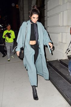 The model stepped out on a chilly March night donning her signature black crop with a luxe neck scarf and a blue duster coat.