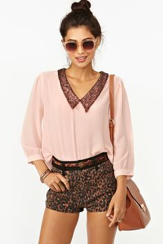 Loose pink blouse with sequin collar, leopard shorts, shades, top knot bun, messenger bag.
