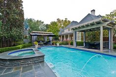 The pool area of this French inspired home reaches the height of luxury. This in-ground, granite pool with an attached hot tub is surrounded by rose beds and luscious landscaping. The pool is close in proximity to the backyards two distinct dining spaces that have curtains around them to give the homeowners and their guests the ultimate privacy.