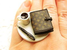 This is for the person who likes to contemplate life and write down their thoughts while drinking coffee! The little diary can open and it is real paper inside so please be sure not to get this ring wet      It is on a silver tone adjustable band that will fit most ring sizes. It measures about 3.8 cm wide.