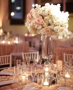 The head table will feature two tall glass vases topped with white hydrangeas, green seeded eucalyptus, pink waxflowers, peachy pink spray roses, blush spray roses and blush stock flowers.
